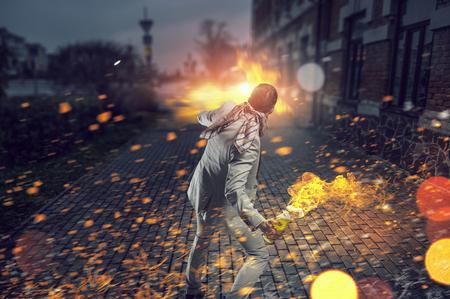 molotov: Young aggressive businessman throw burning molotov cocktail