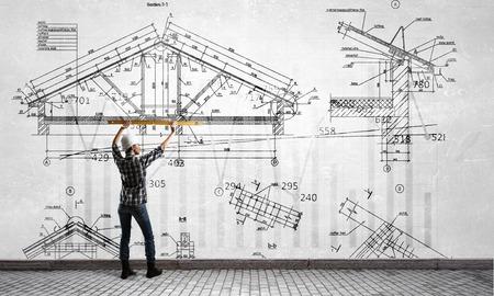 Builder woman taking measures . Mixed media
