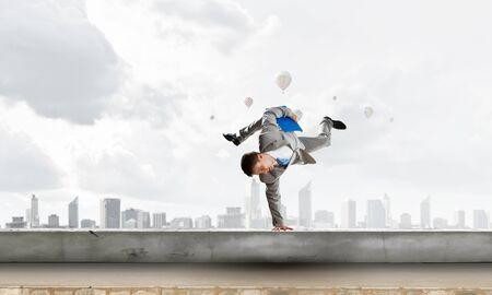 Young businessman breakdancer. Mixed media . Mixed media Stock Photo
