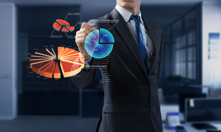 Closeup image of businessman drawing graphs on screen . Mixed media