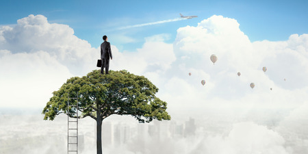 Elegant businessman standing on green tree crown