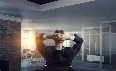 Back view of relaxed businessman sitting on chair with hands on nape. Mixed media Stock Photo