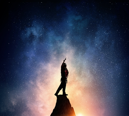 Young brave man alpinist standing on mountain top at night