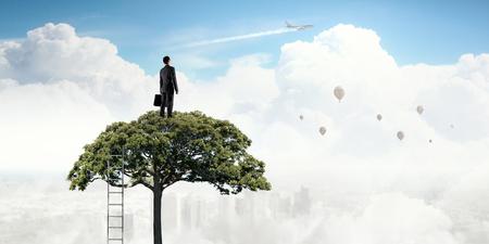 Elegant businessman standing on green tree crown