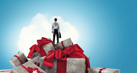 Young businessman standing on stack of gift boxes