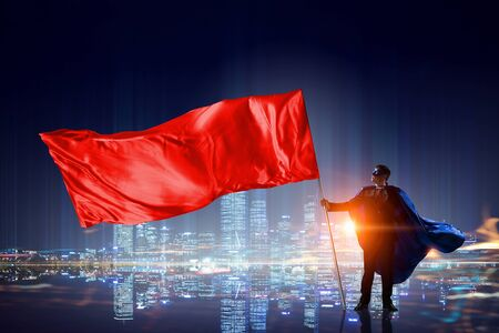 Young businessman with red flag in mask and cape