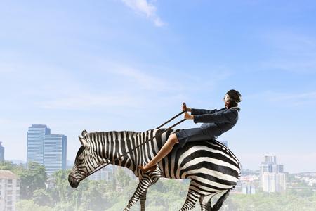 Businesswoman ride zebra . Mixed media Imagens