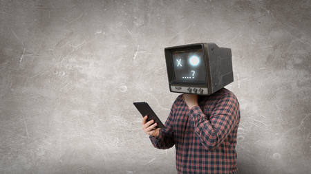 Man with TV monitor instead of head using tablet pc. Mixed media Imagens
