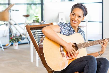 アコースティック ギターを弾く若い女性