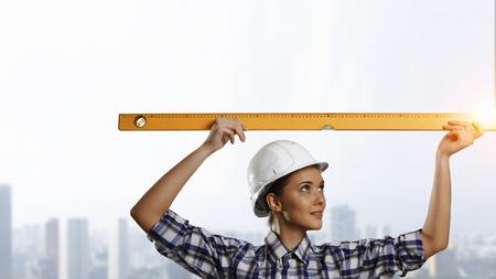 Builder woman taking measures. Mixed media Reklamní fotografie