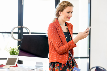 lady on phone: Young woman holding mobile phone in office
