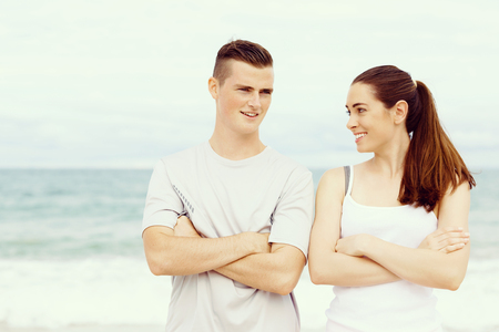 Young couple looking at each other while standing on beach Stock Photo