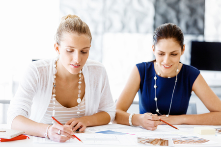 cooperate: Two female colleagues in office