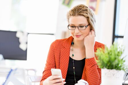 woman on phone: Young woman holding mobile phone in office
