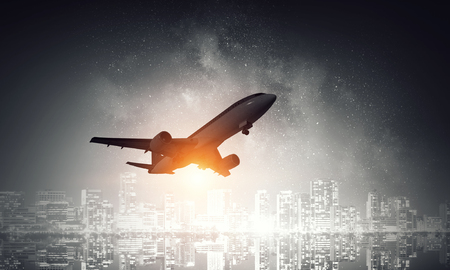Airplane for transportation flying over night scene city Stock Photo