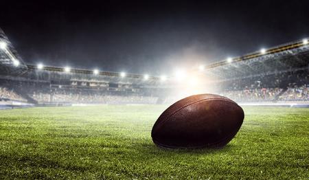 Pro Amerikaans voetbalveld en bal op groen gras. Gemengde media Stockfoto
