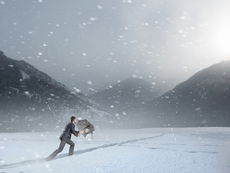 Businessman in suit walking on white now high in mountains