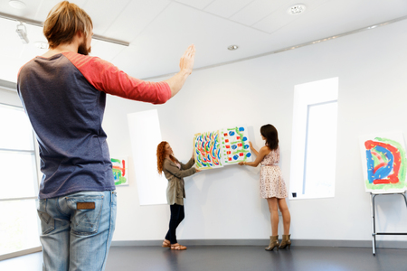 Young artists in gallery hanging painting on walls Imagens