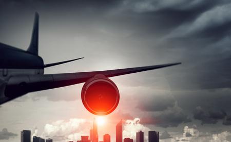 Airplane for transportation flying over modern city scene
