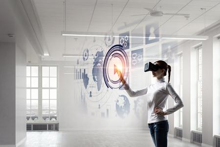 Woman in helmet experiencing virtual reality. Mixed media Stock Photo