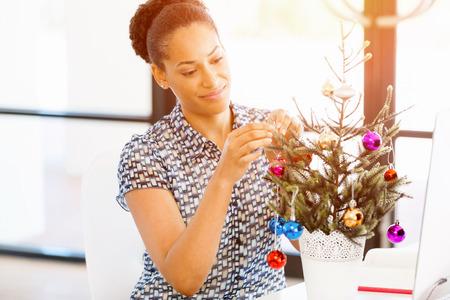 Portret van lachende vrouwelijke kantoor werknemer met kerstboom