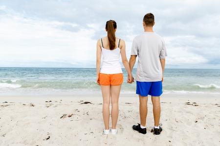 mujer mirando el horizonte: Pareja joven mirando pensativo mientras está parado al lado del otro en la playa Foto de archivo