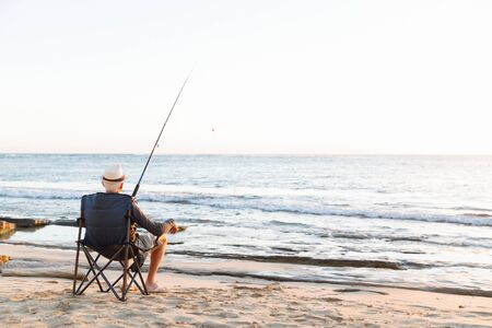 70s: Senior man fishing with rod at seaside