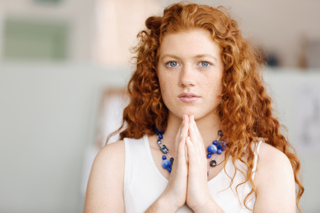 Closeup portrait of a young woman praying Imagens - 80058360
