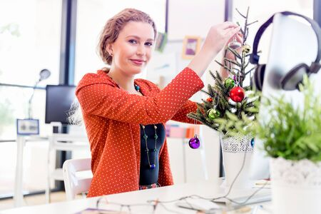 Young woman in office with christmas tree Stock Photo