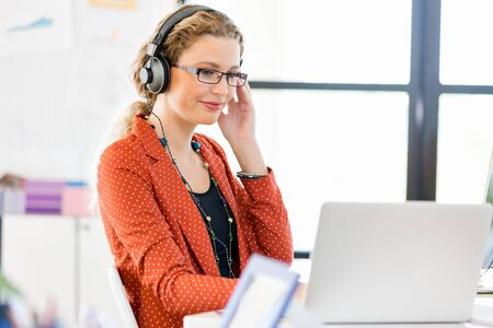 mp3: Young woman listening to the music while working on a computer