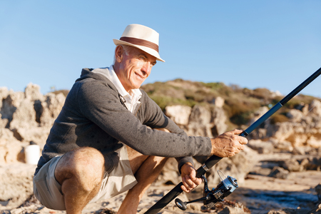 Homme senior pêche au bord de la mer Banque d'images - 80064520
