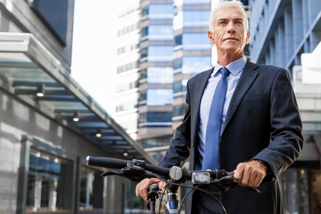 welldressed: Successful businessman riding bicycle