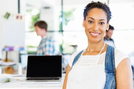 Portrait of smiling afro-american office worker in offfice with her colleagues Stockfoto
