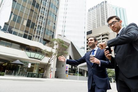 Dos jóvenes empresarios gritando por un taxi Foto de archivo - 80345279