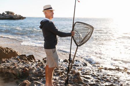 granddad: Senior man fishing at sea side