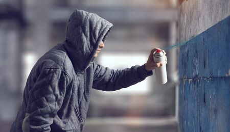 vandal: Guy drawing with spray . Mixed media Stock Photo
