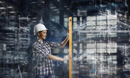 Builder woman taking measures Stock Photo