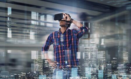 experiencing: Man in virtual helmet . Mixed media Stock Photo