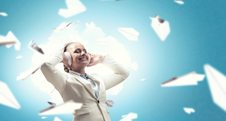 hands free device: Woman wearing white headphones. Mixed media Stock Photo