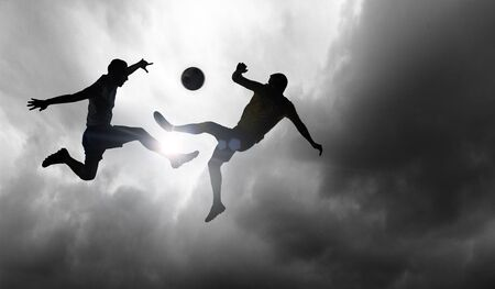 Silhouettes of two soccer players