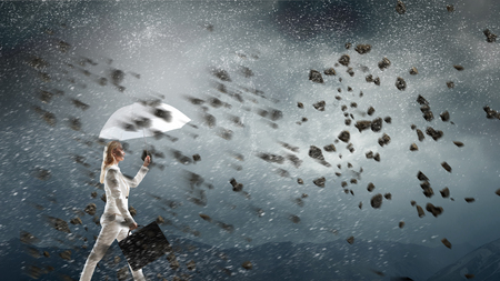 Young blond businesswoman with white umbrella walking against the wind. Mixed media Stock Photo