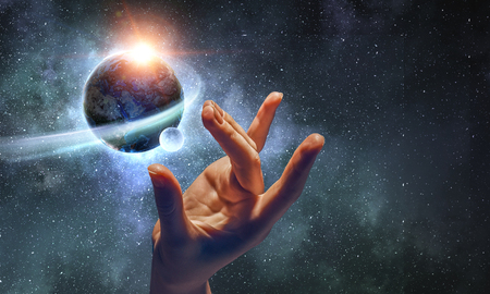 Female hand touching Earth symbolizing faith and religion. Elements of this iamge are furnished by NASA Reklamní fotografie