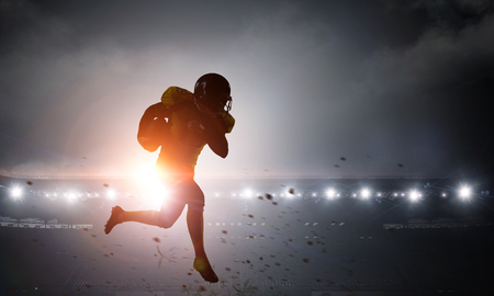 Silhouette of american football player at stadium. Mixed media