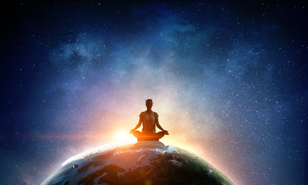 Young woman sitting on Earth planet and meditating. 스톡 콘텐츠