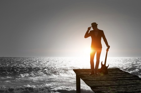 Silhouette of man in hat with guitar in hands. Mixed media Stock Photo