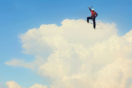 Alpinist man climbing white cloud high in sky. Mixed media Stock Photo
