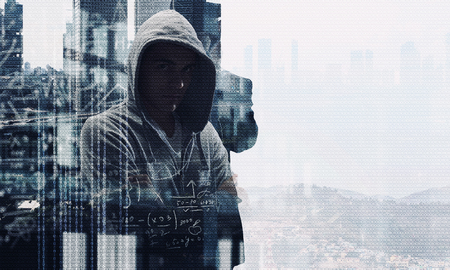 Young man haker wearing hoody on binary code background. Mixed media