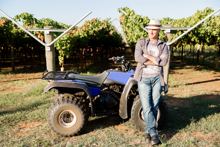 Man standing next to truck in vineyard