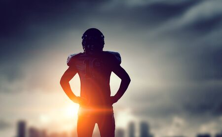 Silhouette of american football player on cityscape background. Mixed media