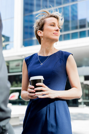 Businesswoman with coffee in a city Banco de Imagens